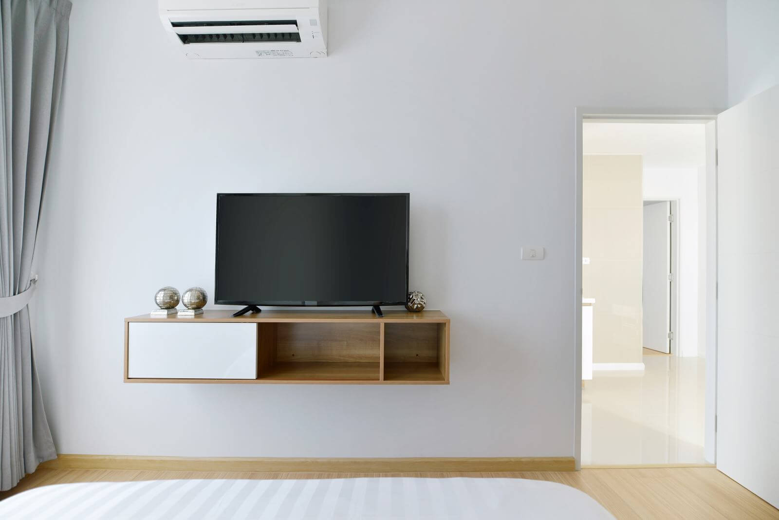 Modern Empty bedroom with led tv on white wall and wooden shelf